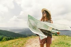Stylish traveler hipster woman  with sunglasses hat and windy ha. Ir holding map on top of mountains and sky, travel or exploring concept, space for text Stock Photography