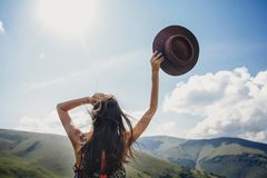 Stylish traveler woman looking at mountains. hipster girl on top. Of mountain, raising hands and holding hat in sky. space for text. atmospheric epic moment Stock Photos