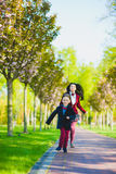 Stylish trendy boy and woman or son with mother playing outdoor Stock Image