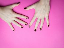 Stylish trendy female manicure. Beautiful young woman`s hands on pink and blue background. royalty free stock photos