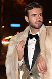 Stylish, trendy flamboyant man with golden suit, bow tie and fur coat outdoors Stock Images