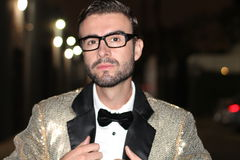 Stylish, trendy flamboyant man with golden suit, bow tie and glasses looking sharp outdoors Royalty Free Stock Images