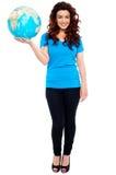 Stylish trendy girl posing with globe in hand Stock Photo