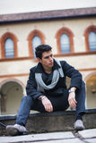 Stylish trendy young man sitting outdoor in old historical building Stock Image