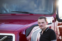 Stylish truck driver and modern dark red semi truck. A young truck driver involved in professional freight over long distances, stands next to his contemporary Stock Photos