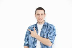 A stylish unshaven man in a shirt points to a copy of the space on a white wall, as something nice shows, has a smiling look, adve. Rtises a product. Look here! stock images