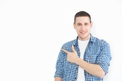 A stylish unshaven man in a shirt points to a copy of the space on a white wall, as something nice shows, has a smiling look, adve royalty free stock images