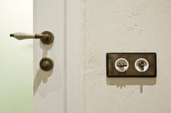 Stylish vintage brass light switchers and door knob Royalty Free Stock Image