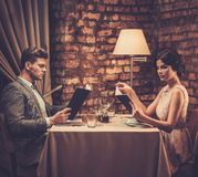 Stylish wealthy couple with menu Stock Images