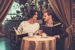 Stylish wealthy couple with menu Royalty Free Stock Photo