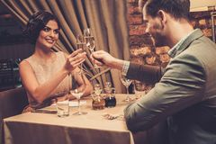 Stylish wealthy couple toasting with champagne Stock Image