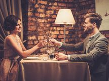 Stylish wealthy couple toasting with champagne. In a restaurant Stock Photos