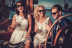 Stylish wealthy friends having fun on a luxury yacht royalty free stock images