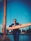 Stylish wealthy man on a luxury wooden regatta Stock Image