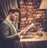 Stylish wealthy man with menu Royalty Free Stock Photography