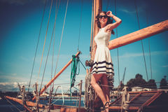 Stylish wealthy woman on a luxury wooden regatta Stock Images