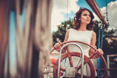 Stylish wealthy woman on a luxury wooden regatta Royalty Free Stock Images