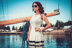 Stylish wealthy woman on a luxury wooden regatta Royalty Free Stock Image