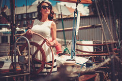 Stylish wealthy woman on a luxury wooden regatta Royalty Free Stock Photos