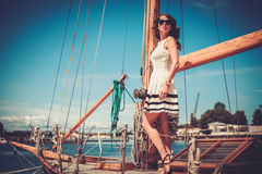 Stylish wealthy woman on a luxury wooden regatta.  Royalty Free Stock Images