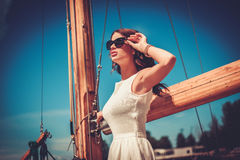 Stylish wealthy woman on a luxury wooden regatta stock photography