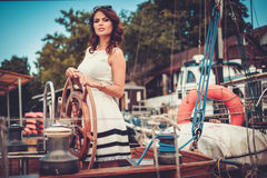 Stylish wealthy woman on a luxury wooden regatta.  Stock Photo