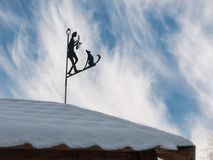 Weather vane on a roof. Stylish weather vane on a roof in the form of the musician with a saxophone and a dog Royalty Free Stock Photography