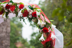 Stylish wedding arch with red roses and white lilies, garden. Wedding ceremony Royalty Free Stock Image