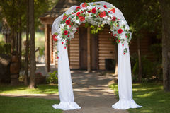 Stylish wedding arch with red roses and white lilies. Garden, wedding ceremony Stock Image