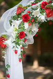 Stylish wedding arch with red roses and white lilies, garden. Wedding ceremony Royalty Free Stock Photos