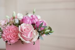Stylish wedding bouquet bride of pink roses, white carnation and green flowers and greens with ribbons lying on pastel royalty free stock photos