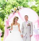 Stylish wedding ceremony elegant blonde bride and groom outdoors. Creative stylish wedding ceremony elegant blonde bride and groom outdoors royalty free stock image