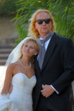 A stylish wedding couple. Adult men with  long red hair in a tuxedo,  tie with a gold ring on his little finger and black glasses is holding the chin of his Stock Photo