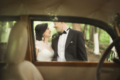 Stylish wedding couple, bride, groom kissing and hugging near retro car in autumn Royalty Free Stock Photography