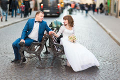 Stylish wedding couple bride in white dress and elegant groom sitting on a bench holding hands Stock Photo