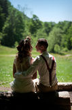 Stylish wedding couple bride in white dress and elegant groom sitting on a bench in the park Royalty Free Stock Images