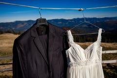 Stylish wedding dress and suit hanging on hanger. Amazing mountain landscape  background Royalty Free Stock Photo