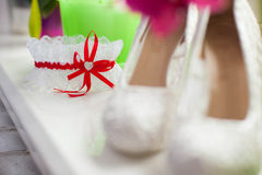 Stylish wedding garter with red ribbon and small heart. In the center, beautiful high heels royalty free stock image