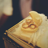 Stylish wedding rings in the heart-like box stand on the lace pi Royalty Free Stock Images