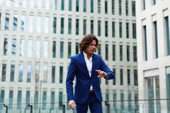 Stylish, well-dressed man looking at the clock waiting for his companion Royalty Free Stock Image