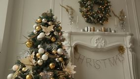 Stylish white christmas interior with decorated fir trees, fireplace, lanterns, lamps, candles, wreath, bumps and gifts. Stylish white christmas interior with stock video