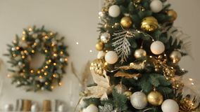 Stylish white christmas interior with decorated fir trees. Comfort home with christmas tree full of golden decorations. With wreath and lights of garlands on stock footage