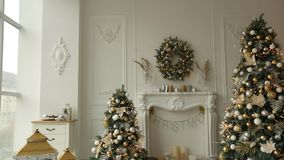 Stylish white christmas interior with decorated fir trees, fireplace, lanterns, lamps, candles, wreath, bumps and gifts. Stylish white christmas interior with stock footage