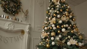 Stylish white christmas interior with decorated fir trees, fireplace, lanterns, lamps, candles, wreath, bumps and gifts. Stylish white christmas interior with stock video footage