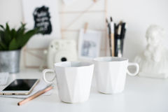 Stylish white desktop, home office interior details with two cof. Fee cups, scandinavian style stock images