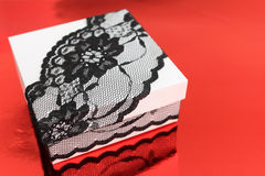 Stylish white gift box, decorated with black lace ribbon on red background Royalty Free Stock Photos