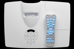 Stylish white home cinema projector with remote, top down view. Stylish white home cinema projector with remote, isolated on black, top down view Stock Image