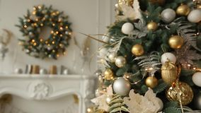 Stylish white interior with fir christmas trees, and wreath full of golden decorations, toys, lights and garlands