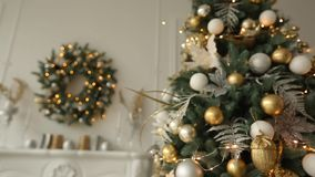 Stylish white interior with fir christmas trees, and wreath full of golden decorations, toys, lights and garlands stock footage