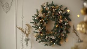 Stylish white interior with fir christmas trees, and wreath full of golden decorations, toys, lights and garlands. Wreath on background. New Year`s Eve stock footage
